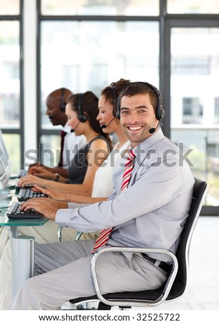Friendly young businessman with folded arms in a call center