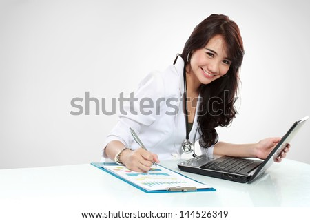 friendly young doctor working in office - stock photo