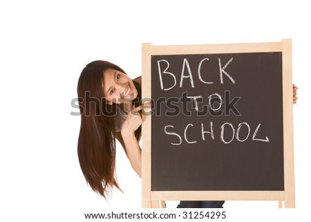 Friendly young ethnic High school girl student of mixed Vietnamese and Chinese race standing by chalkboard and pointing to the text - back to school - stock photo