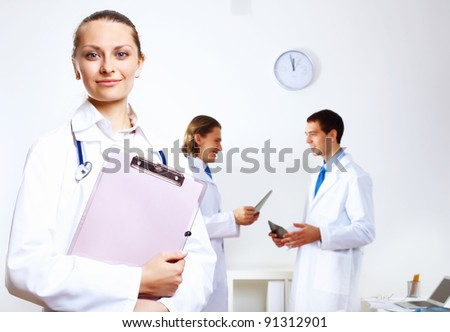 Friendly young female doctor in uniform in medical office - stock photo