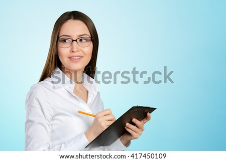 friendly young smiling businesswoman with clipboard and pen - stock photo