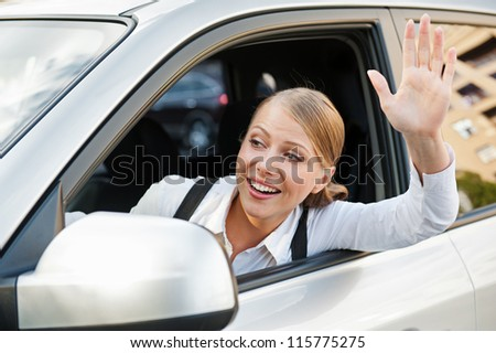 friendly young woman sitting in the car and waving her hand - stock photo