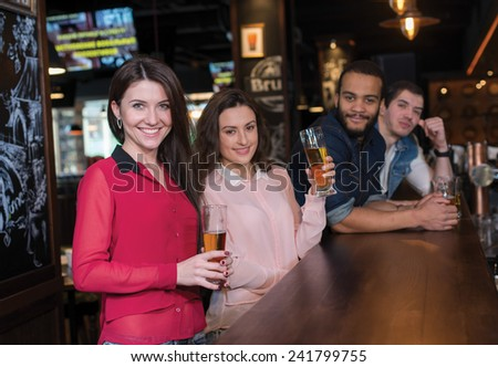 Friends and beer. Four friends are drinking beer in a pub. Girls and guys are smiling - stock photo