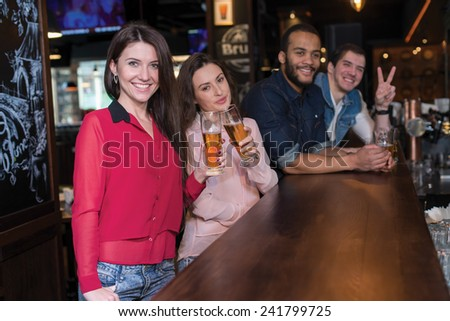 Friends and beer. Four friends are drinking beer in a pub. Two smiling girls are on the foreground with glasses of beer - stock photo
