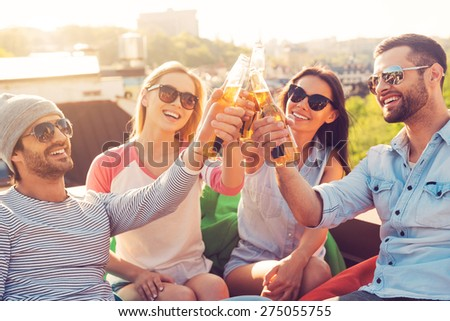 Friends and beer. Four young cheerful people cheering with beer and smiling while sitting at the bean bags on the roof of the building - stock photo