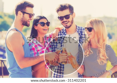 Friends and beer. Group of happy young people cheering with beer and smiling while standing outdoors together - stock photo