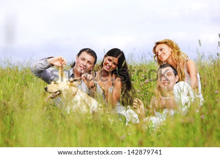 friends and dog in green grass field - stock photo