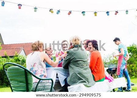 Friends and neighbors on long table celebrating party toasting with drinks - stock photo