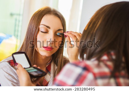 Friends applying makeup at home.