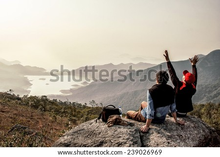 Friends are happy that they got on top of mountain  - stock photo