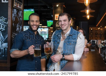 Friends are having fun with beer. Portrait of two handsome friends in a pub with glasses of beer - stock photo
