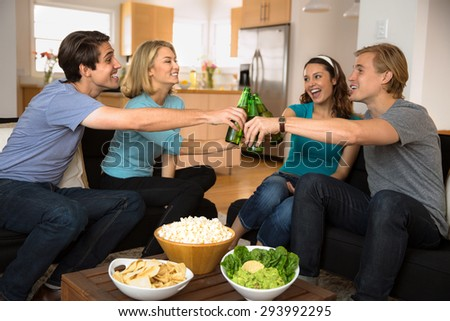 Friends at home drinking and cheers beer drinks celebrating and happy during holidays - stock photo
