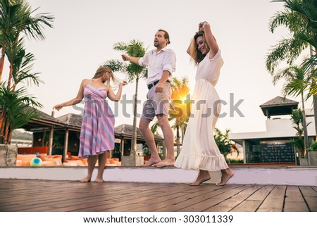 Friends at party dancing in a open air club - Three happy and smiling persons having fun and listening music at a private party - stock photo