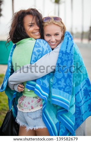 Friends at Sunset on the Beach in California wrapped in a towel together