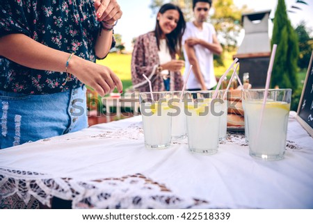 Friends at table with fresh lemonade having fun - stock photo
