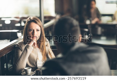 Friends at the bar, he is giving her bad news - stock photo
