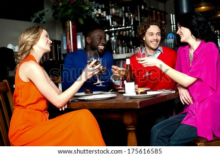 Friends at the bar raising their glasses for a toast - stock photo