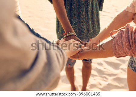 Friends at the beach putting hands together. Multiracial group of young people with hands in stack at the beach. - stock photo
