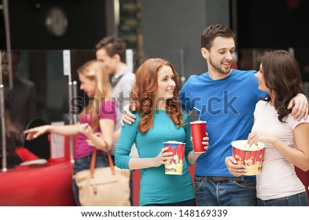 Friends at the cinema. Cheerful young people talking at the cinema hall - stock photo