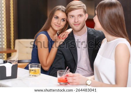 Friends at the party. Selective focus on a beautiful young couple sitting with their female friend at the bar counter and having a drink - stock photo