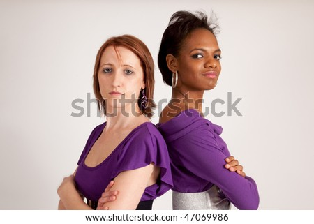 Friends back to back with arms crossed, racially mixed