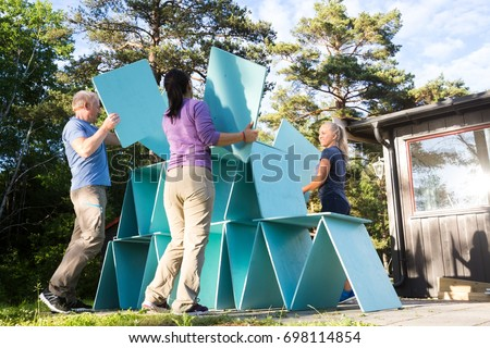 Friends Building Pyramid With Wooden Planks In Forest