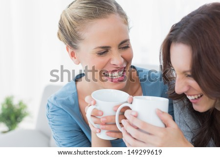 Friends bursting out laughing while having coffee sitting on the sofa - stock photo
