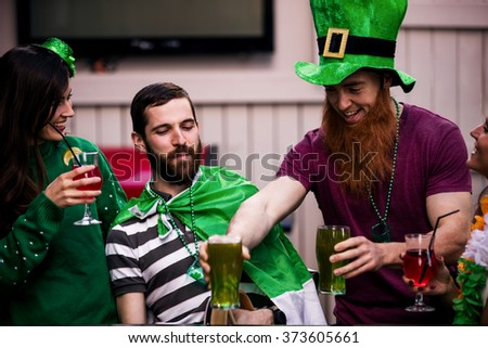 Friends celebrating St Patricks day with drinks in a bar - stock photo