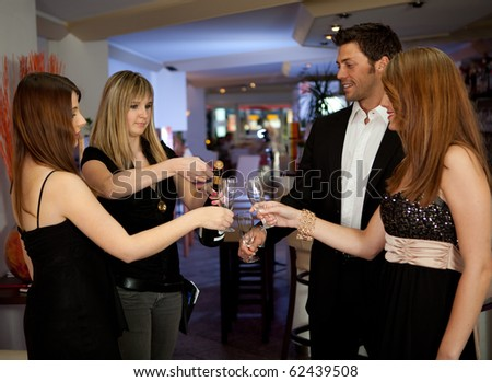 Friends celebrating with bottle of champagne. Focus on the bottle - stock photo