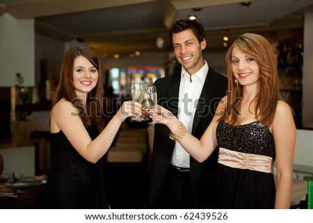 Friends celebrating with champagne. Focus on glasses - stock photo