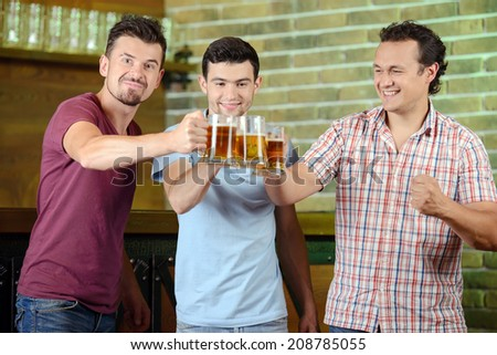 Friends cheering. Three happy soccer fans drinking beer at the pub - stock photo
