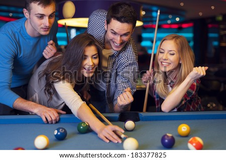 Friends cheering while they friend aiming for billiards ball - stock photo