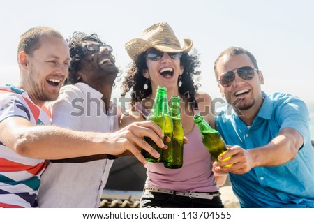 Friends cheers at the beach on a sunny afternoon, a fun party gathering outdoors by the sea - stock photo