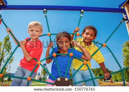 Friends climbing the net at the playground - stock photo