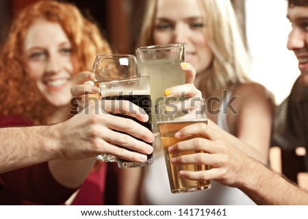 Friends clink glasses together in a cheer at a bar.