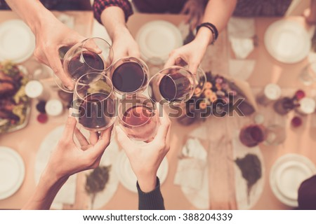 Friends clinking glasses above dinner table - stock photo