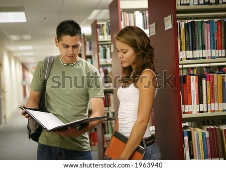 Friends comparing notes in a school library - stock photo
