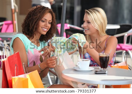 Friends comparing purchases in a cafe - stock photo