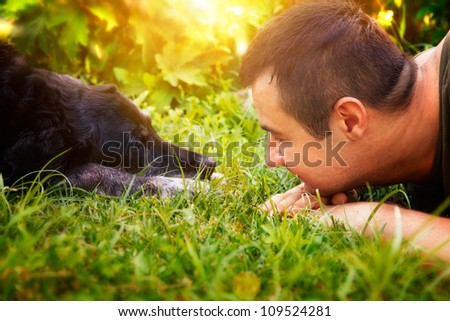 Friends concept. Man and labrador retirever dog are lying in summer grass - stock photo