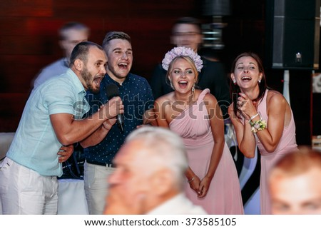 Friends congratulating the bride and groom on their wedding day - stock photo