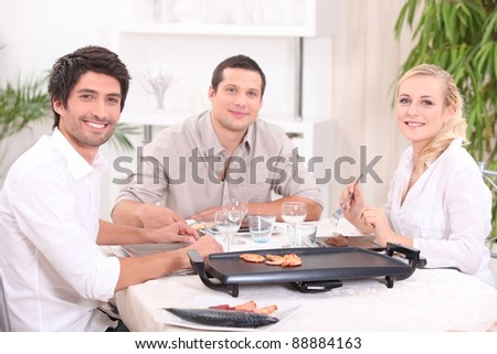 Friends cooking dinner on a tabletop hot plate - stock photo