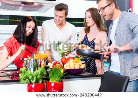 Friends cooking spaghetti and meat in domestic kitchen - stock photo