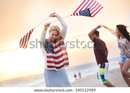 Friends Dancing on the Beach in California at sunset - stock photo
