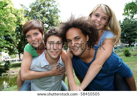 Friends doing piggyback in park - stock photo