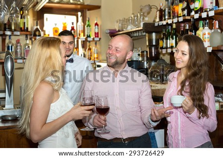 Friends drinking and chatting with barman at bar counter - stock photo