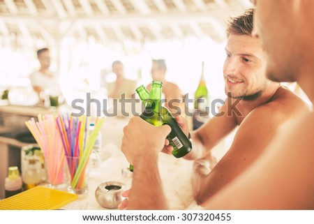 Friends drinking beer in beach bar - stock photo