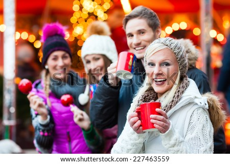 Friends drinking mulled wine and eating crystalized appkes on German Christmas Market - stock photo
