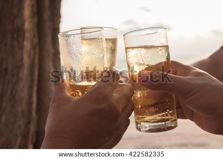 friends drinking whiskey on party on the beach. - stock photo