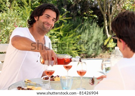 Friends drinking wine outdoors - stock photo
