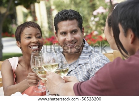 Friends drinking wine outdoors, head and shoulders - stock photo
